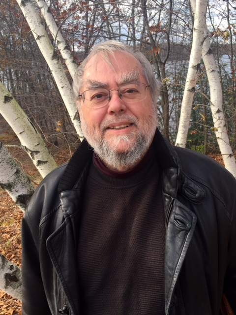 An image of Ron Morin--a bearded man with glasses, a sweater, and a leather jacket standing in front of a stand of birch trees