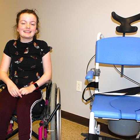 Photo of a young woman with her new assistive equipment