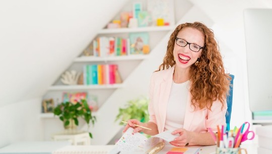 Lara Casey Isaacson, a red-headed lady in a pale pink blazer, laughs at the camera holding a paper planner.