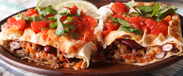 Photo of chicken burritos topped with tomatoes and cilantro.