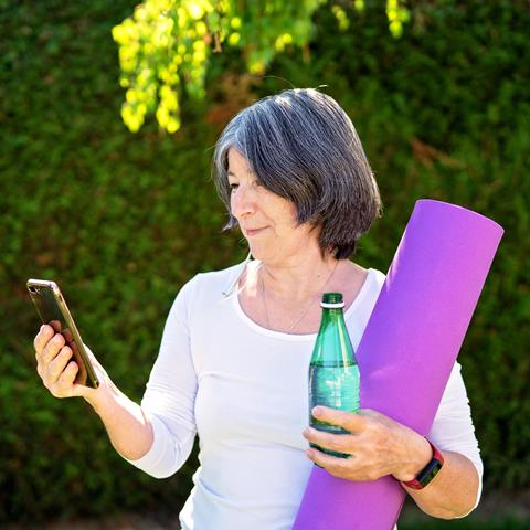 An older woman stands outside with a cellphone, a yoga mat, and a water bottle.