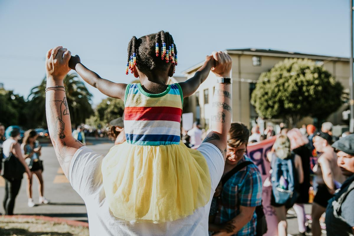 Child wearing rainbow colors on adult's shoulders at Pride 2018