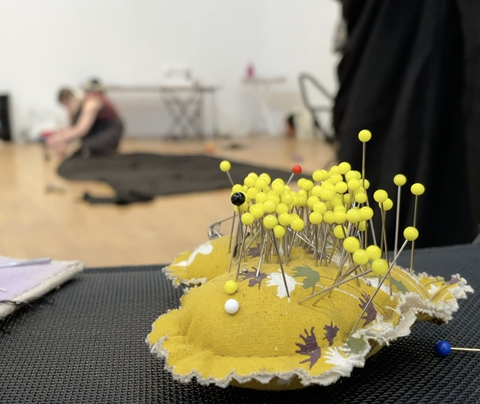 A yellow heart shaped pin cushion sits in the foreground whilst an out of focus young person works in the background. The pin cushion has many bright yellow pins in and the person in the background is sewing dark material.