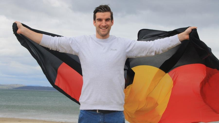 Image of Jake standing on the beach with the Australian Aboriginal flag.