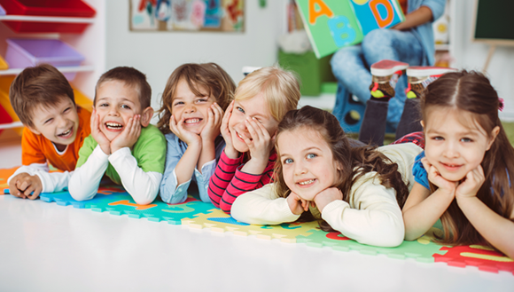 Six children laying on their stomachs in a classroom and smiling