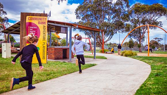 Children running in bright fun park. Sign with words Community Bank Adventure Playground.