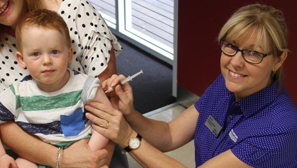 Nurse giving young boy immunisation
