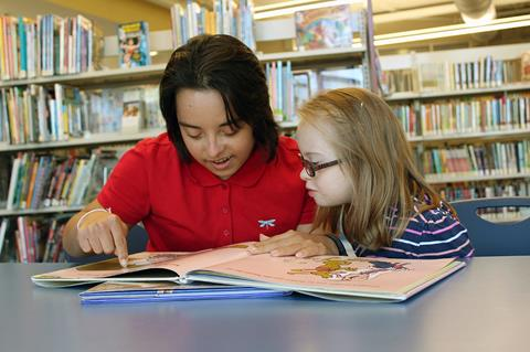 Photo of Megan McCormick reading with a child with Down syndrome.