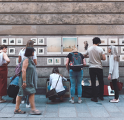 Image of people on a sidewalk looking at several pieces of art on a building wall.