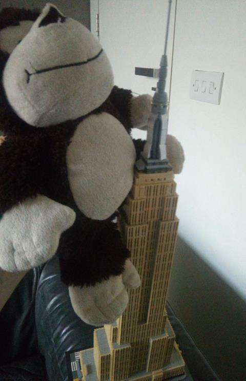 Photo of a teddy monkey beside a model of the Empire State Building