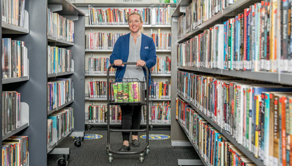 Lady pushing trolley of books through library