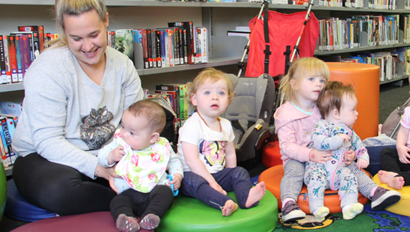 Toddlers sitting on cushions at the library
