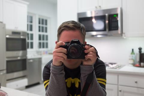 Photo of Andy Meredith, a teen with Down syndrome, holding a camera.