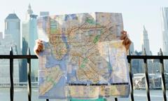 A person holds up a large map of a city.