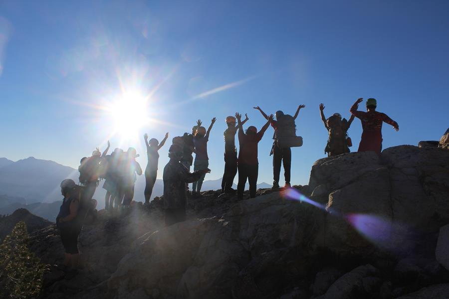"""A group of youth with backpacking gear """"power pose"""" on top of a mountain, with dramatic views behind them and blue sky and bright sun shadowing their faces."""