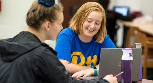 Girl in Pitt shirt looking at laptop