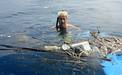 Man in water with trash