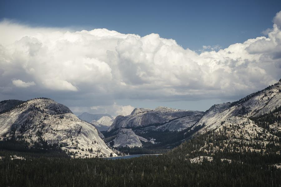A beautiful view of Yosemite's clear blue Tenaya Lake, nestled below granite mountains. The photo was taken from a distance, with a layer of fluffy clouds above.