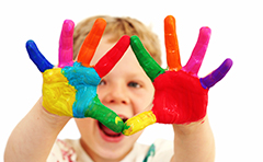 Photo of young child with paint on hands