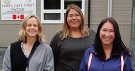 CAMH's Dr. Samantha Wells, Krystine Abel and Dr. Renee Linklater outside the nursing station in Sandy Lake