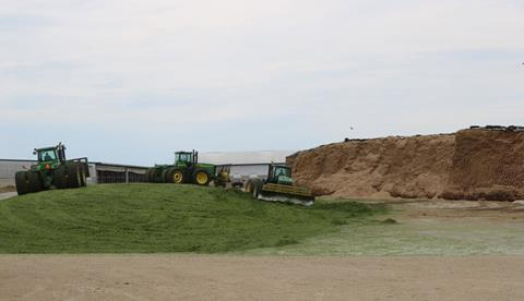 tractors moving silage into a pile