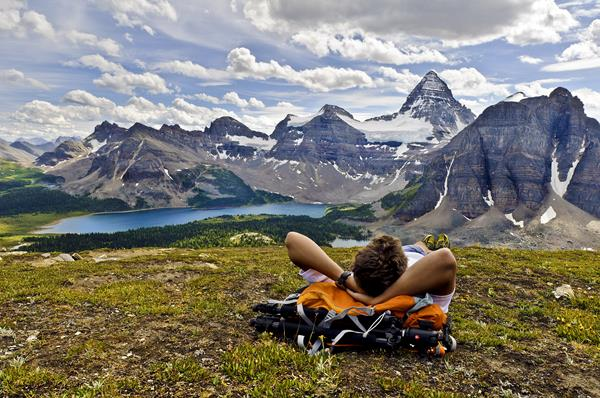 Hiker relaxing in front of Mt Assiniboine