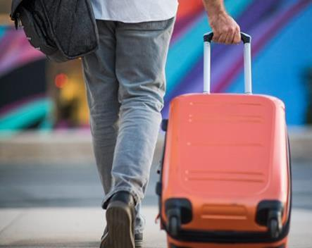 Person dragging a suitcase on wheels