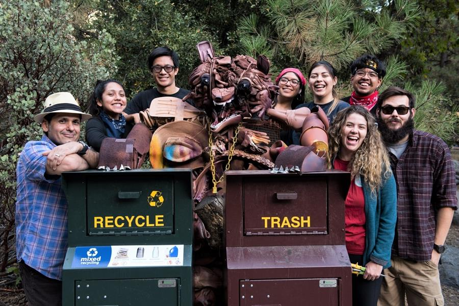 """Volunteers pose with a """"found art""""sculpture of a bear created using items collected during apark-wide cleanup event."""