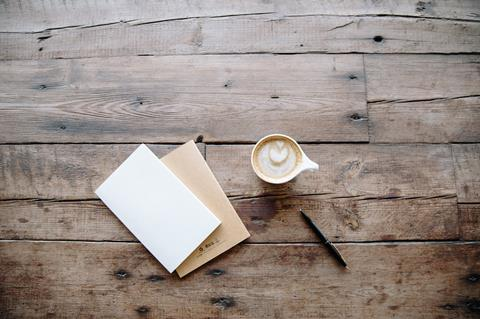 Envelopes and coffee on table