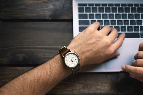 Man's arm with watch resting on laptop
