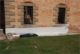 The poultice material has been applied to the foundations of the Penitentiary