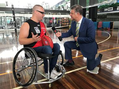 Man in a wheelchair being interviewed by a television sports presenter