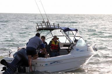 Man climbing into a leisure fishing boat where two young people wait for him.