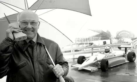 Murray Walker holding phone and umbrella while smiling in front of F1 car