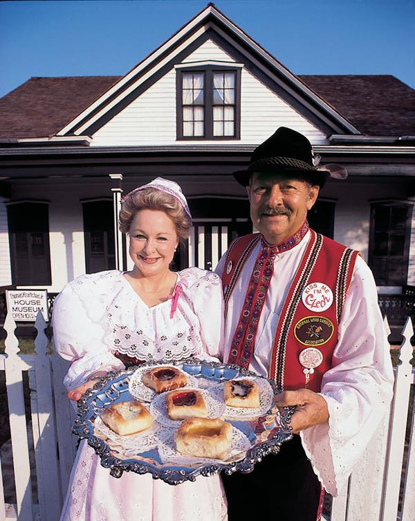 Two people stand holding a silver platter with several kolaches