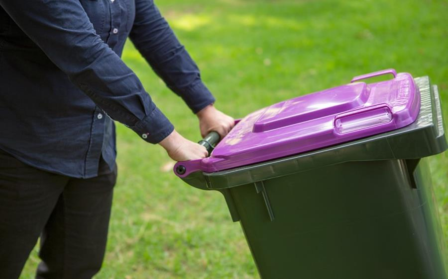 Person putting out purple glass recycling bin