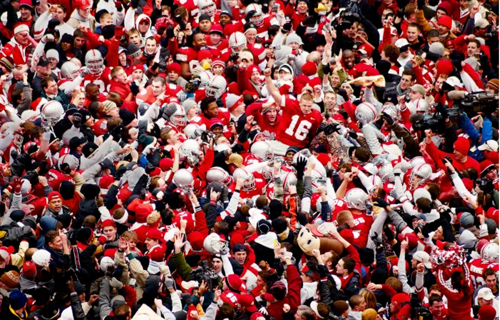 Ohio State Football team and fans celebrating on field after win