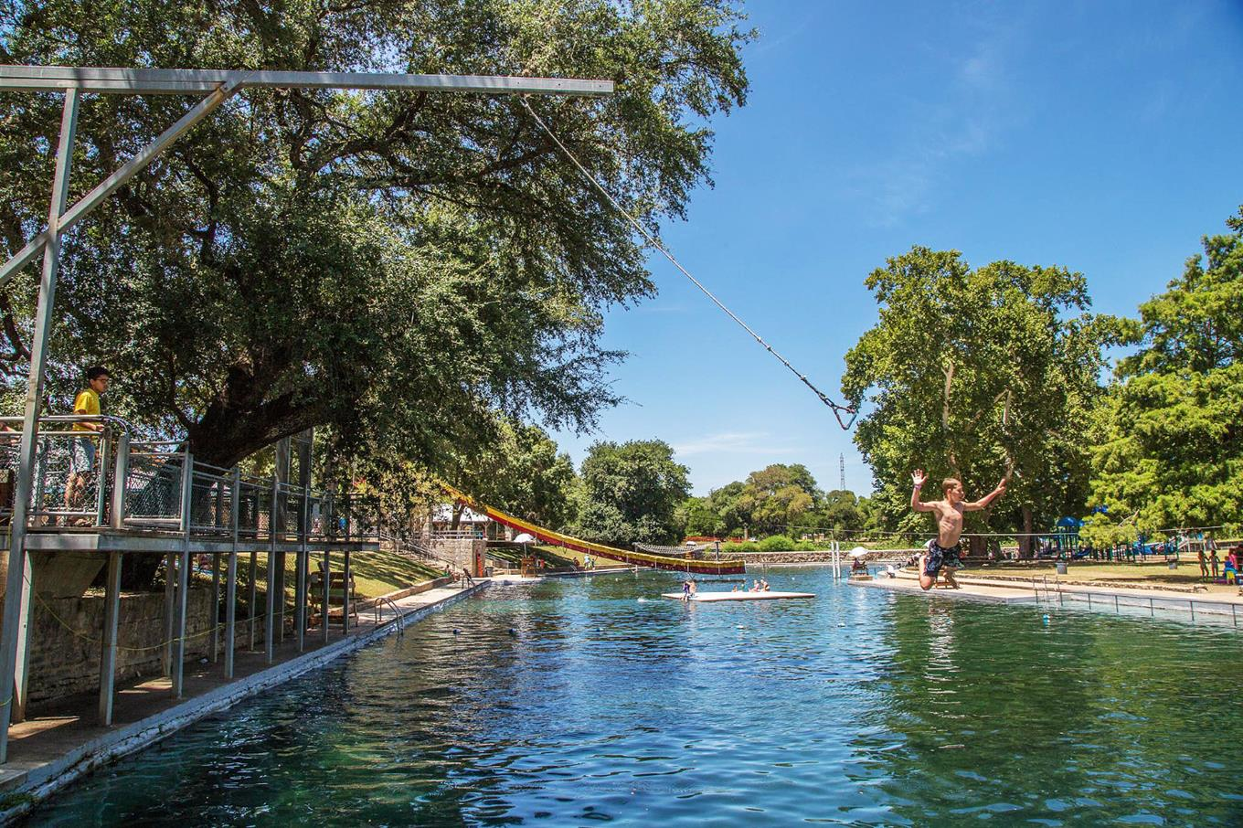 A boy jumps into the water off a rope swing