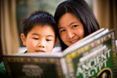 A teacher and child read a book together