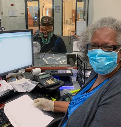 Photo of customer wearing a mask and being served by a Clerk & Comptroller who is also wearing a mask and sitting behind a glass barrier