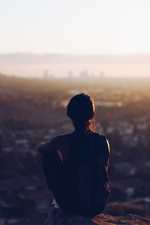 Observe - photo shows a silhouetted figure sat on a rock staring at a landscape; a cityscape in the backgroun out of focus.