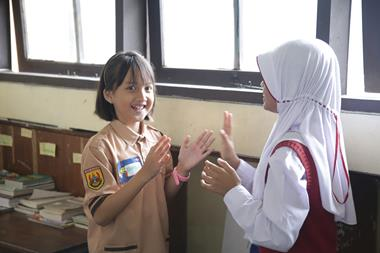 Two girls play a clapping game