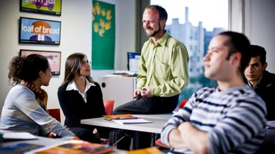 Teacher discusses with adult learners