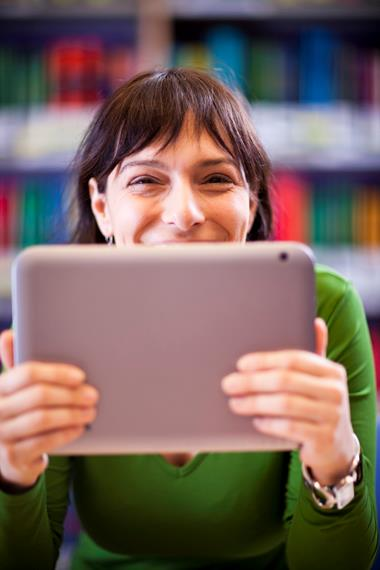 A young woman holds a tablet computer