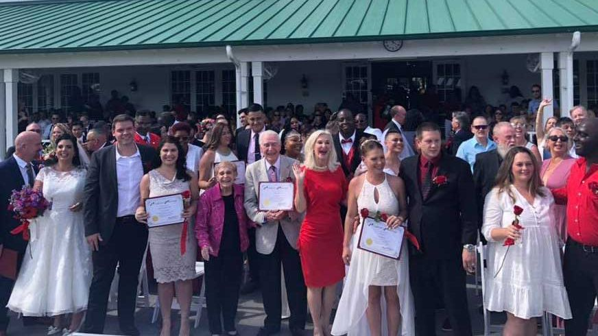Photo of couples following Valentine's Day Group Wedding Ceremony