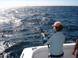 woman fishing from back of boat with a fishing rod
