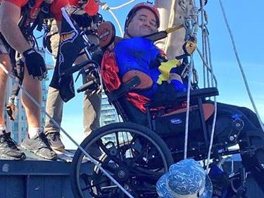 Image of a man in a wheelchair being lowered off a building for Easter Seals' Drop Zone