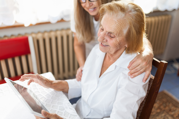 happy elderly lady on an iPad with carer