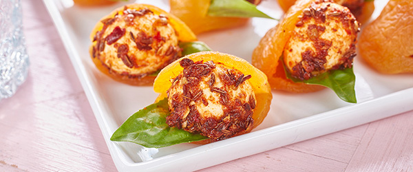 Photo of dried apricots stuffed with small, spiced bocconcini cheese balls with basil garnish.