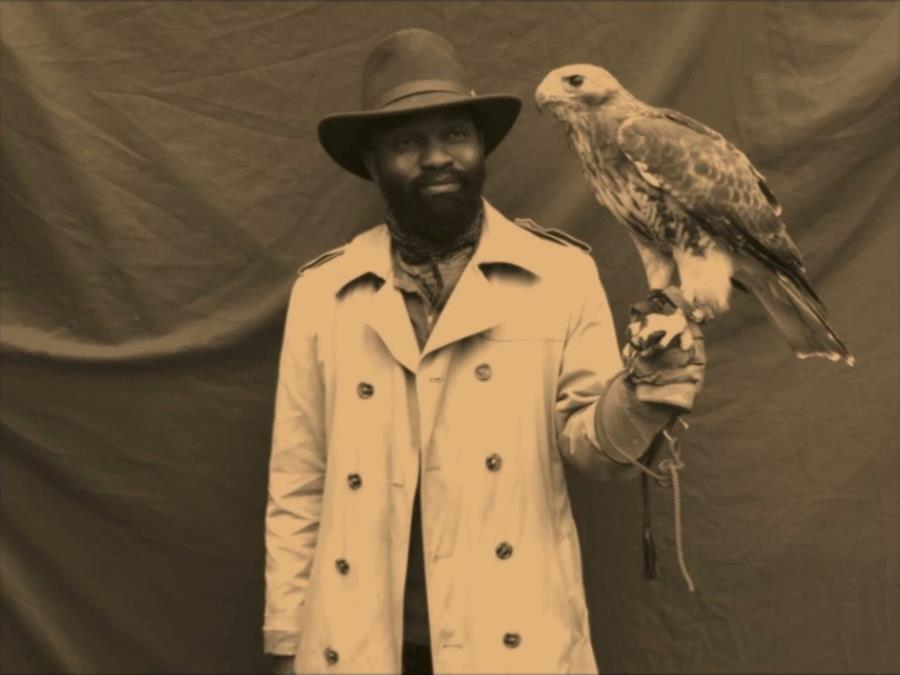 Image description: A sepia photograph of a black male standing in front of a dark cloth and holding a large bird of prey. The man wears a smart light coloured coat with buttons and a wide brimmed hat.